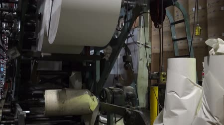 gazete : Tilt up shot of the large paper rolls that feed into an industrial scale newspaper offset printing press.