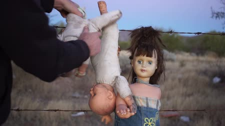 farpado : Static shot of a mentally unstable or crazy person hanging toy dolls on a barbed wire fence and grabbing the neck in a motion of strangling it.