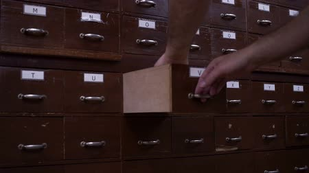índice : Side view shot of an anonymous man opening the drawer on a wooden card catalog and looking through the index cards inside. Vídeos