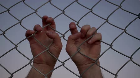 закат : Closeup evening or dusk shot of the two hands of an anonymous male person grabbing a chain link metal wire fence from the opposite or other side of the viewer. Стоковые видеозаписи