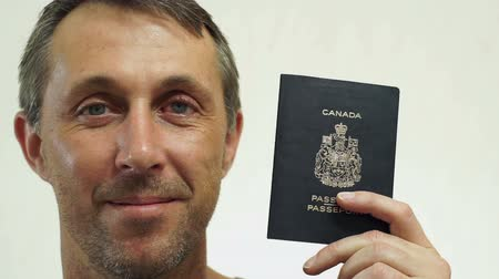 gümrük : Closeup portrait shot of a happy middle aged male with a Canadian passport ID which is needed to go on vacation or take business trips outside of Canada to other countries of the world. Stok Video