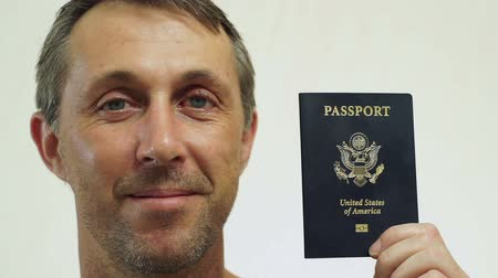 pas : Closeup portrait shot of a happy middle aged male with an American passport ID which is needed to go on vacation or take business trips outside of the USA to other countries of the world. Dostupné videozáznamy