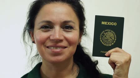 pas : Closeup portrait shot of a happy middle aged woman with a Mexican passport ID which is needed to go on vacation or take business trips outside of Canada to other countries of the world. Dostupné videozáznamy