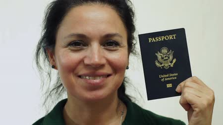 gümrük : Closeup portrait shot of a happy middle aged woman with an American passport ID which is needed to go on vacation or take business trips outside of the USA to other countries of the world. Stok Video