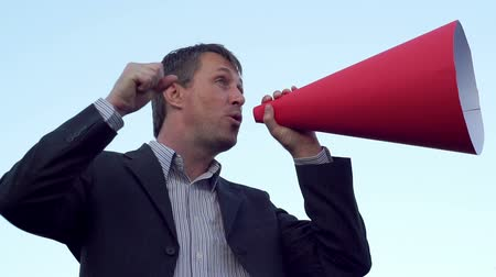 подиум : Side view shot of a man wearing a suit standing against a clear blue sky and making an announcement through a red rolled paper bullhorn while shaking his fist and pointing his finger.
