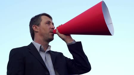 подиум : Side view shot of a calm man wearing a suit against a clear blue sky and making an announcement through a red rolled paper bullhorn.