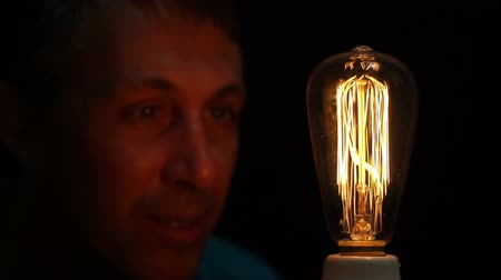 szórakoztatás : Close up shot of a man fascinated by an antique style filament bulb with his face barely lit by the soft warm yellow light of the retro light source.