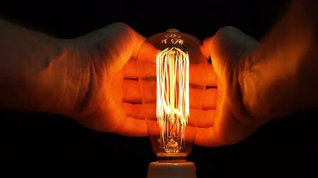 izzók : Close up point of view or POV shot of an anonymous man warming his hands with the heat produced by an antique retro style carbon filament bulb.
