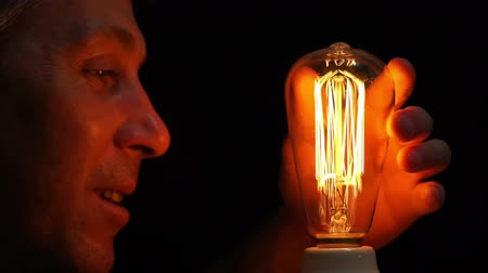 szórakoztatás : Close up side view shot of a man fascinated by an antique style filament bulb touches it and taps the glass bulb with his finger.