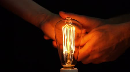 történelmi : Close up shot of an anonymous caring man holding the hand of an anonymous woman and helping her warm it by rubbing it and holding it close to a retro style carbon filament bulb. Stock mozgókép