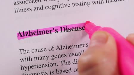 teste : Close up shot of a person that could be a doctor or a nurse highlighting the medical term or condition Alzheimers Disease.