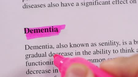 zdůraznit : Close up shot of a person that could be a doctor or a nurse highlighting the medical term or condition Dementia.