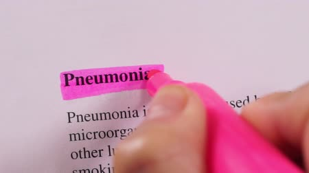 zdůraznit : Close up shot of a person that could be a doctor or a nurse highlighting the medical term or condition Pneumonia.