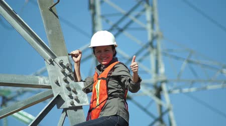 jóváhagyás : Female technician in a safety vest and hard hat standing on the side of a high tension electrical tower visually inspects the situation and gives the viewer a thumbs up gesture.