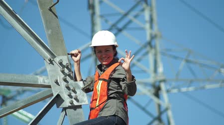 assess : Female technician in a safety vest and hard hat standing on the side of a high tension electrical tower visually inspects the situation and gives the viewer an OK gesture.
