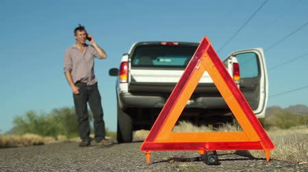 országúti : Male in the distance talking on a mobile phone with his broken down truck with hazard lights on parked on the side of the road and an emergency marker reflective triangle in the foreground.