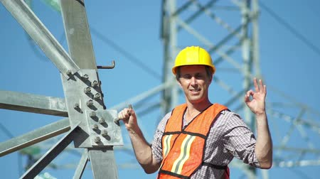 assess : Closeup shot of a male technician in a safety vest and hard hat standing on the side of a high tension electrical tower visually inspects the situation and gives the viewer an OK gesture.