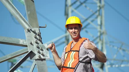inspeção : Close up shot of a male technician in a safety vest and hard hat standing on the side of a high tension electrical tower visually inspects the situation and gives the viewer a thumbs up gesture.