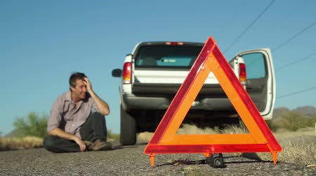 országúti : Male in the distance sits on the roadside with his broken down truck with hazard lights on parked on the side of the road and an emergency marker reflective triangle in the foreground.
