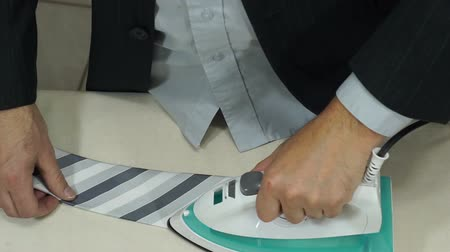 gravata : High angle shot of an anonymous businessman or office worker in a suit and dress shirt getting ready and ironing the wrinkles out of his tie.