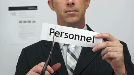 makas : Male office worker or businessman in a suit and tie cuts a piece of paper with the word personnel on it as a personnel reduction business concept. Stok Video