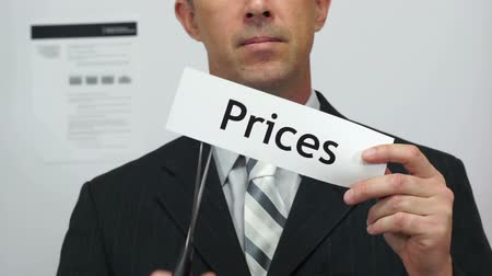 vágás : Male office worker or businessman in a suit and tie cuts a piece of paper with the word prices on it as a price reduction business concept. Stock mozgókép