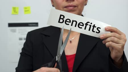 dikmek : Female office worker or business woman cuts a piece of paper with the word benefits on it as a benefits reduction business concept.