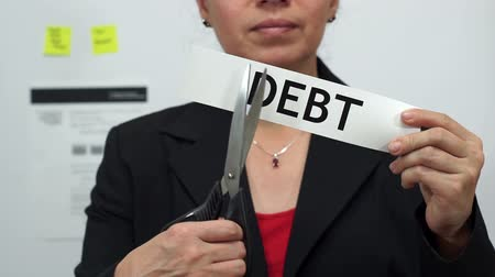 adósság : Female office worker or business woman cuts a piece of paper with the word debts on it as a debt reduction business concept. Stock mozgókép