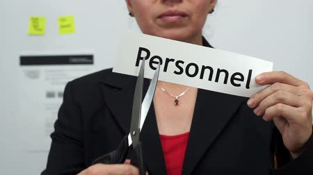 recursos : Female office worker or business woman cuts a piece of paper with the word personnel on it as a personnel reduction business concept.
