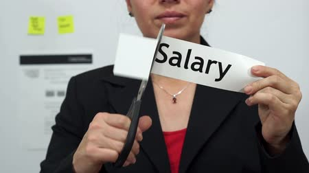 dikmek : Female office worker or business woman cuts a piece of paper with the word salary on it as a salary or pay reduction business concept. Stok Video