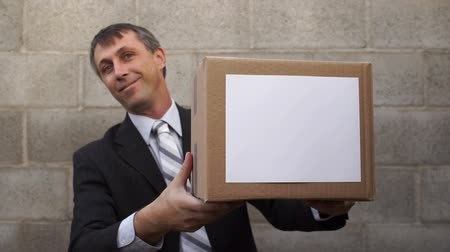 giveaway : Businessman waiting in a nice suit standing up against a wall holding a box that he hands to the viewer. Stock Footage