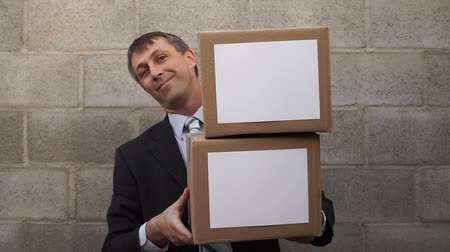 giveaway : Businessman waiting in a nice suit standing up against a wall holding two boxes and he looks out from behind the packages. Stock Footage