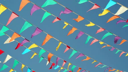 festividades : Panning shot against a clear blue sky background of colorful string pennant triangle flags used for celebrations or grand openings blowing in the wind.