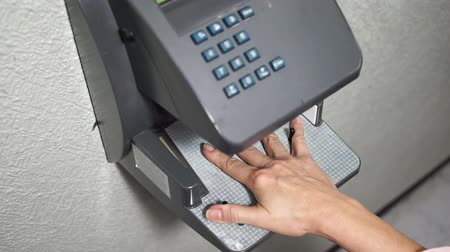 áttekinthetőség : Close up shot of an employee biometric handpunch or time clock that records when a worker goes on or off the job.