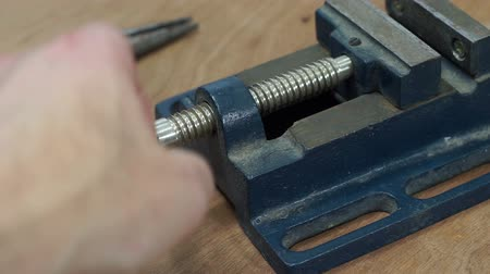 trabalhador manual : Anonymous person closes a bench top metal machinists vice used for clamping small objects while they are being worked on by a craftsman or tradesperson