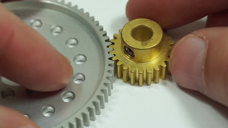 engrenagem : Close up shot of an anonymous person testing the meshing of the teeth between a hub mounted spur gear and a pinion spur gear used in small mechanical devices like robots and other machines. Vídeos