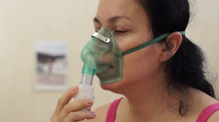 oksijen : Side shot of a woman using a breathing mask nebulizer treatment to help her with a respiratory or lung illness.