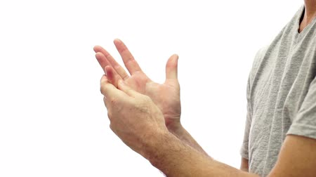 esneme : Closeup of an anonymous man isolated on a white background and rubbing his sore and painful hand and fingers and knuckles.