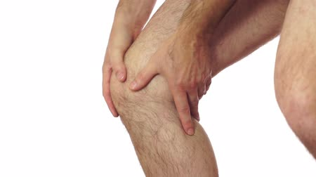kolano : Closeup of an anonymous man isolated on a white background and rubbing his sore and painful leg knee joint.