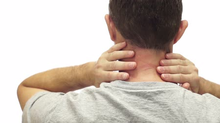 egészségügy és az orvostudomány : Closeup of the back of a man isolated on a white background and rubbing his sore and painful neck and neck muscles.