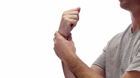 artrite : Close up shot of a male figure isolated on a white background holding his sore wrist that is probably hurting from a painful disease like carpal tunnel syndrome or a work or sports injury.