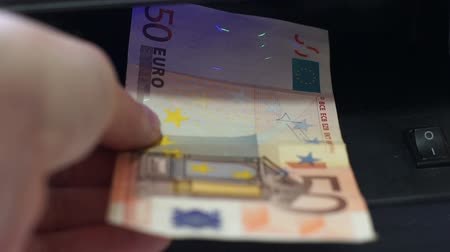 yanliŞ : Closeup shot of an anonymous person putting 50 Euro European Union currency under a black light to check for counterfeit or fake money. Stok Video