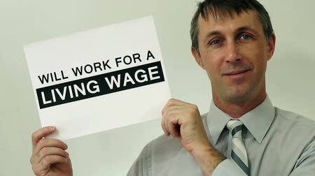 mínimo : Middle aged man wearing a dress shirt and tie holds up a sign that says he will work for a living wage which refers to a wage that is high enough to maintain a normal standard of living.
