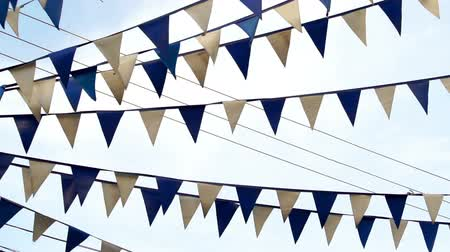 festividades : Panning shot of blue and white pennant flags on strings advertising a grand opening or celebration or event and flapping in the wind against a blue sky. Stock Footage