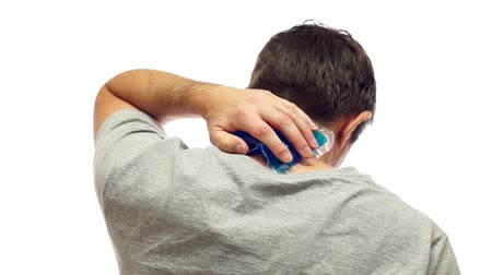 esneme : Middle aged man isolated on a white background rubbing his sore or injured neck with a soothing cold pack to provide him with pain relief.