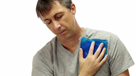 palpitação : Man isolated on a white background rubs a blue cold pack on the front of his shoulder to relieve his muscle or joint pain from an injury or medical condition.