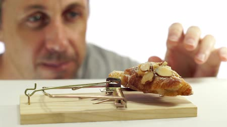 соблазнять : Close up shot of a man looking eagerly at eating a sweet bread that is in a mouse or rat trap which indicates that he should not eat it or is on a diet.