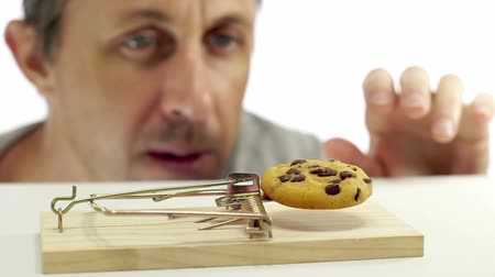 ловушка : Close up shot of a man looking eagerly at eating a sweet cookie that is in a mouse trap which indicates that he should not eat it or is on a diet.