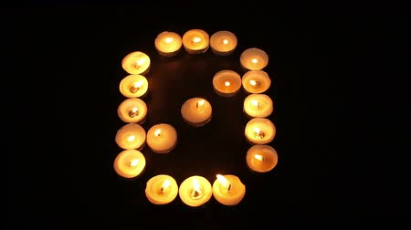 sıfır : Static shot of burning tealight candles arranged like pixel art numeral digits to represent the number zero on a black background. Stok Video
