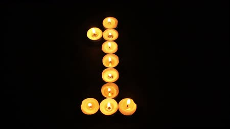 číslo : Static shot of burning tealight candles arranged like pixel art numeral digits to represent the number one on a black background. Dostupné videozáznamy